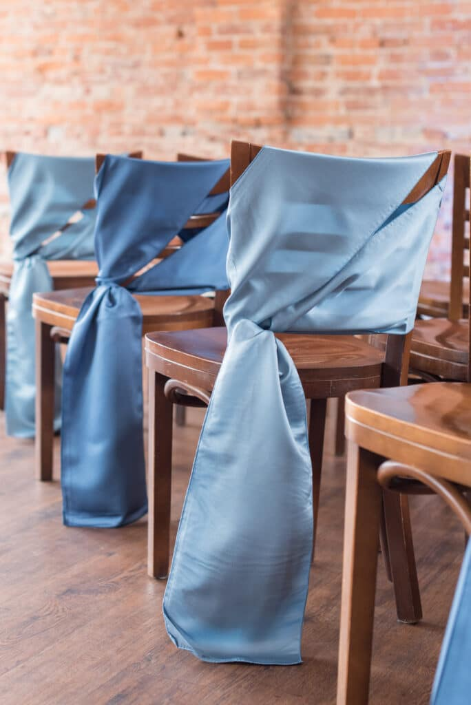 wooden chairs for wedding ceremony with elegant sashes in shades of blue in front of exposed brick wall