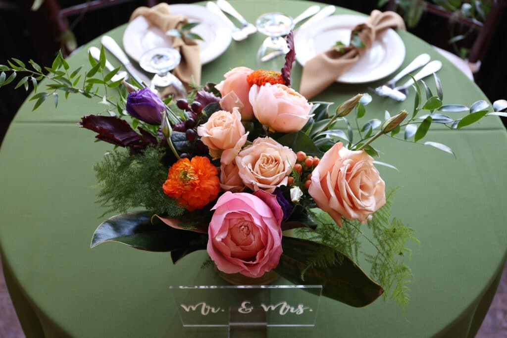 Peach floral centerpiece with greenery on sweetheart table