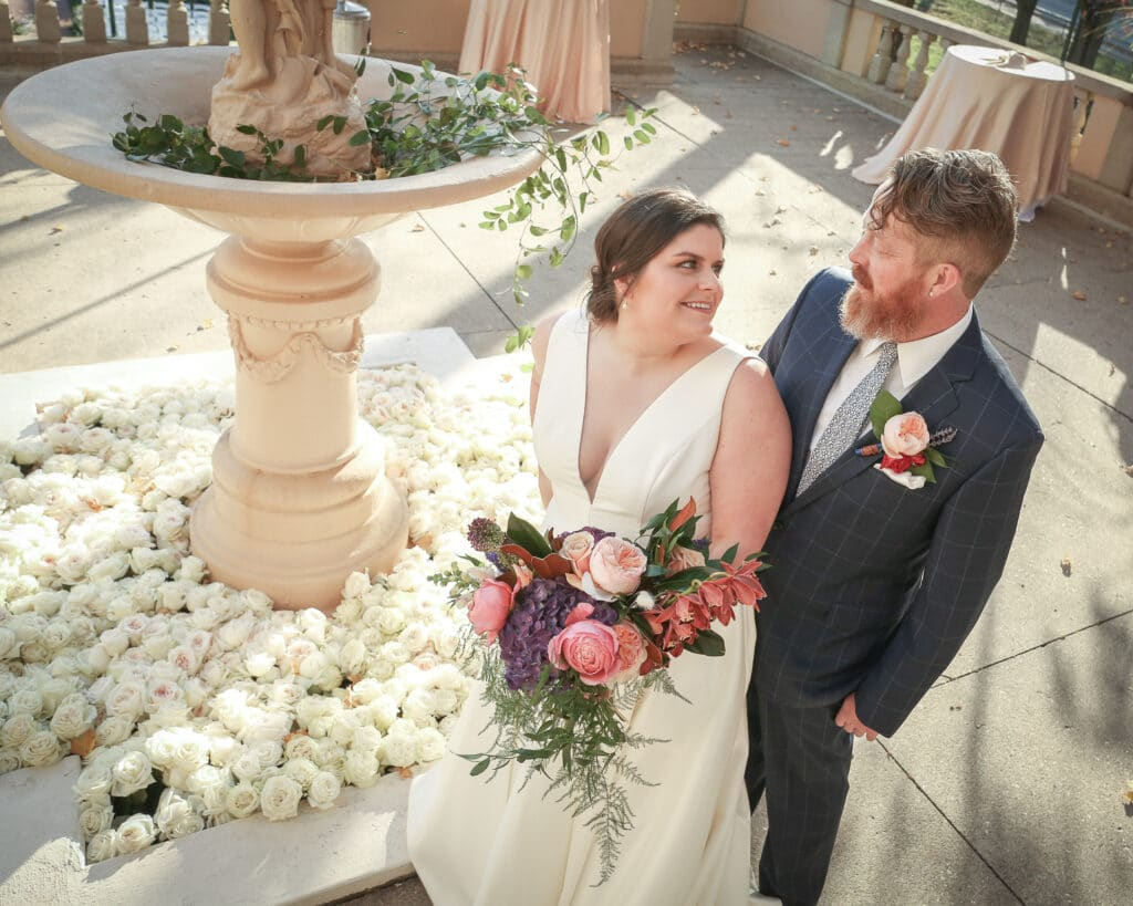 bride and groom in front of rose-filled fountain on the outdoor terrace at fowler house mansion